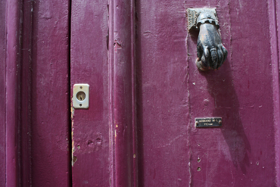 Hand-shaped door knocker on pink door